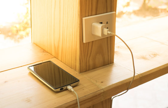 Mobile phone charger plugged on  wooden pole in the coffee shop with sunlight in morning time.