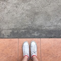 White Sneakers shoes walking on Dirty concrete top view