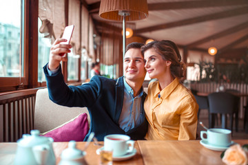 Love couple hugs and makes selfie on phone camera