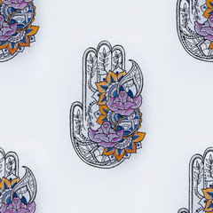 Seamless hamsa pattern with flowers on a white background.