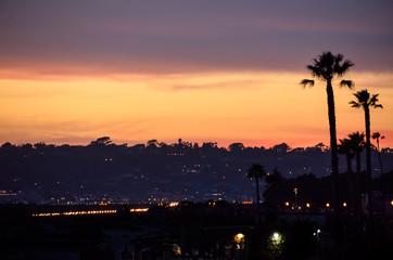 Beautiful sunset with silhouettes of palm trees and San Diego California coast in Coronado island