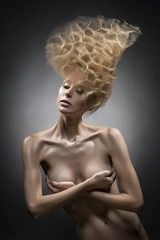 topless girl covering breast with a vanguard hairstyle on a gray background