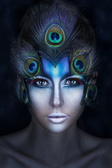the girl's portrait with a vanguard make-up and feathers of a peacock in blue tones