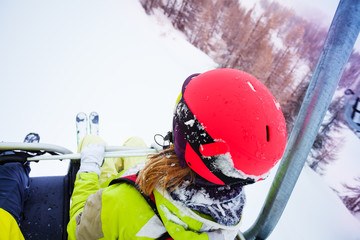 Female skier sitting at chairlift in high mountain