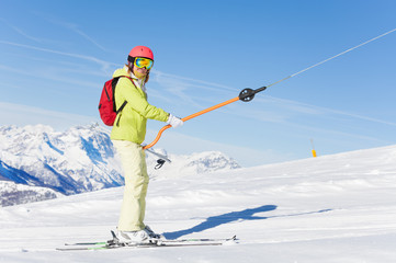 Female skier lifting on a button lift at sunny day