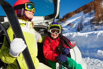 Woman and son in skiing suits sitting on car trunk