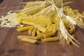 Various types and shapes of dry pasta with spikelets of wheat on the brown wooden background.