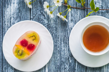 Still life with cup of tea and cake on the wooden background