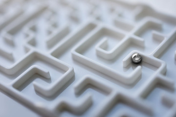 White labyrinth and metal ball, complex problem solving concept.