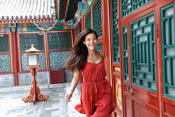 Wall Mural - Beautiful asian model happy lifestyle. Chinese woman running dancing in the wind of happiness and lust for life. Elegant lady in red silk dress at old traditional temple in china. Asia travel.
