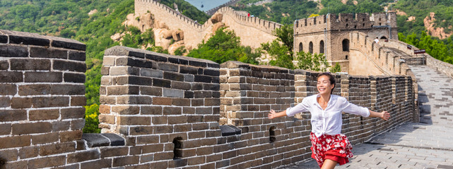 Happy carefree woman traveler running free on Great wall of china. Asia travel. Summer destination popular tourist attraction.