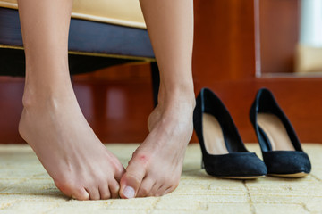 Tired woman removing high heels off feet. Shoe pain concept. Closeup of barefoot lady with painful toes - medical foot problem, nails or discomfort at store or home.