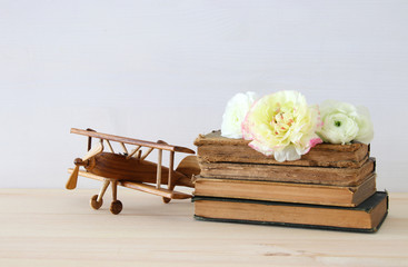 Beautiful spring flowers on the old books next to plane toy