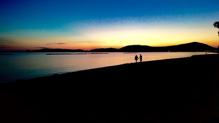 Walking hand in hand on the beach in the Sunset in Sardinia