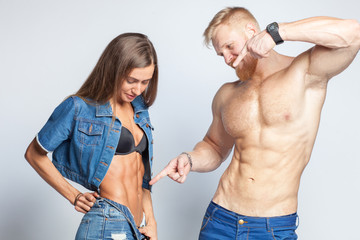 bearded muscular man shows perfect muscular abs of her sporty girlfriend sportswoman isolated on studio background