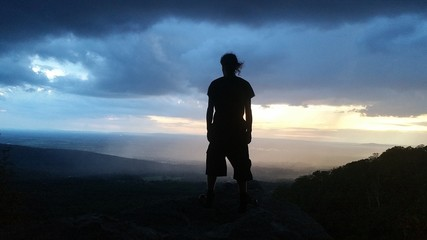 Demonic, evil Looking black silhouette in front of a storm as the sun sets in the mountains. you can see the rain in the background. on the top of South Mountain, a spot called Annapolis Rocks in Maryland. alongside the Appalachian Trail.