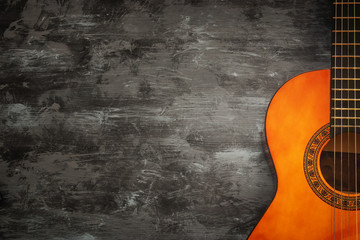 Close up of acoustic guitar against a wooden background