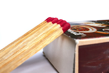 Matches lie against a matchbox, macro shot.