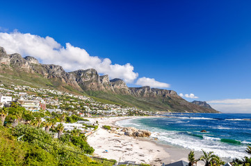 Stunning photo of Camps Bay, an affluent suburb of Cape Town, Western Cape, South Africa. With its white beach, Camps Bay attracts many tourists. Twelve apostles mountain range in the background.