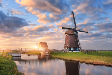 Windmill near the water canal at sunrise in Netherlands. Beautiful old dutch windmill and colorful sky with clouds. Rustic landscape in Holland. Sunny morning. Sky reflected in water. Rural scene