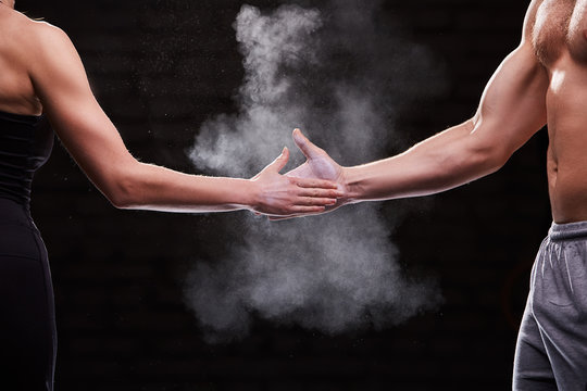 Cropped image of hands of athlete muscular man and woman against dark background.