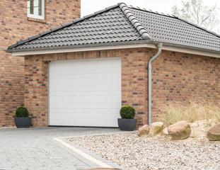 Gemauerte Garage mit einem weißen Tor