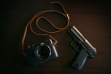 Image of vintage photo camera and a gun. They both shoot.