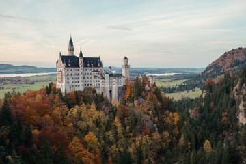 Fotobehang Kasteel Germany. Famous Neuschwanstein Castle in the background of trees with yellow and green leaves and valley.