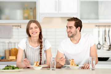 Young couple eating pasta on kitchen table