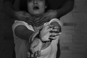 Young woman with tied hands subjected to violence, closeup