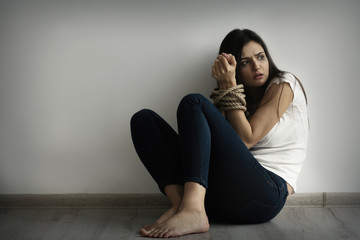 Woman with tied hands sitting on floor against light wall