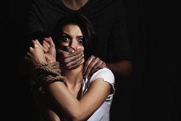 Young woman with tied hands subjected to violence in darkness
