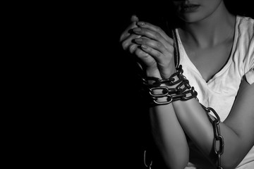 Woman with chained hands in darkness