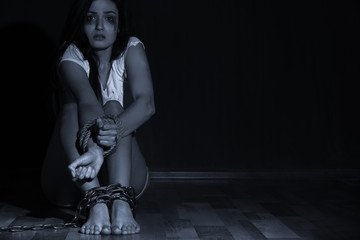 Woman with chained legs and tied hands in darkness