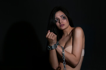Woman with chained hands on dark background