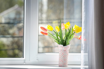 Vase with beautiful tulips on windowsill