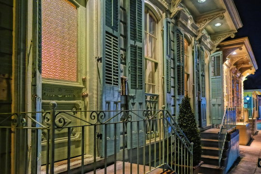 A colorful facade, entry doors in a row, and porches in The French Quarter of New Orleans.