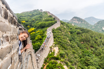 Wall Mural - china travel tourist having fun waving hello at the Great Wall in Badaling smiling happy at camera. Woman tourist traveler enjoying her summer vacation holidays in Asia. Multicultural model.