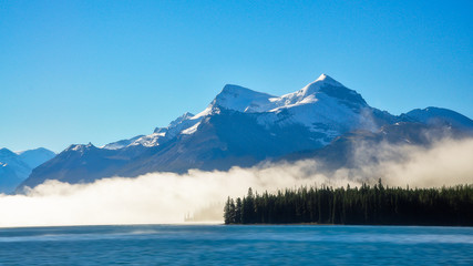 Fog raising over the water in the morning at lake Maligne in Jasper National Park, Canada.