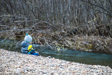 Little baby boy is fishing on the bank of a mountain river with a fishing rod in his hands