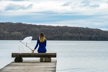 A lonely girl is sad with an umbrella sitting on a bench in the rain on a scribbler near the sea