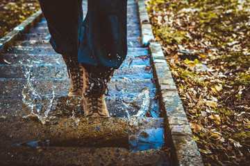 A man climbs the stairs and steps into puddles with his feet. Tourist shoes in the water.