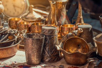 old copper metal glasses and pitcher on counter in sunday flea market. Antique bazaar