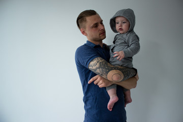 Handsome tattooed young man holding cute little boy on white background