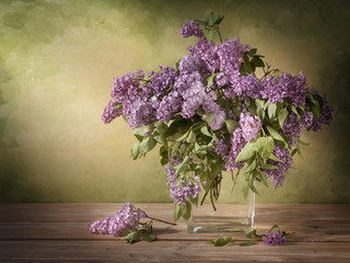 Still life A bouquet of lilac in a glass jug on a wooden table with a picturesque background