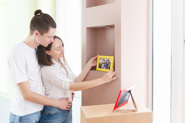 Happy young family at new home. Couple having fun and unpacks boxes with books and photos.