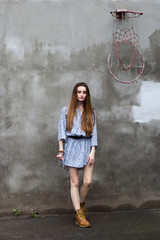 girl in dress and boots near a concrete wall