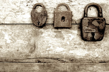 Three old rusty locks on wooden background. Sepia