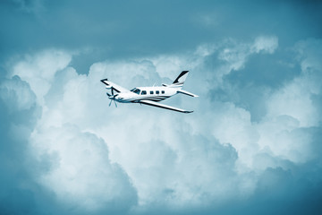 Single turboprop aircraft.. Small private plane flying in blue clouds. Wall mural