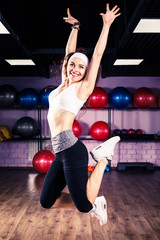Jumping fitness girl doing zumba dancing exercises in gym